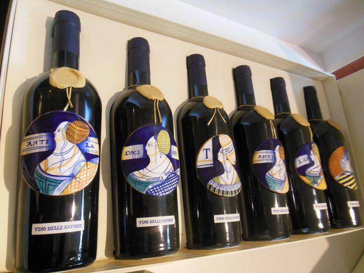 Bottiglia di vino, della tenuta Masselina, impreziosita da un medaglione in ceramica dipinto a mano.