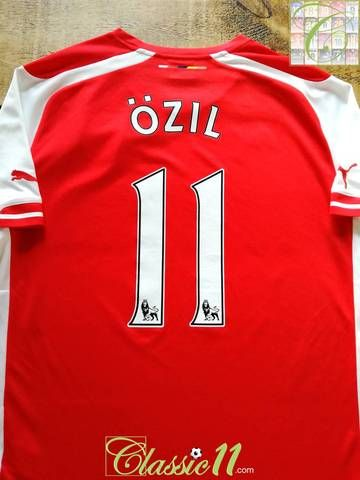 56ddc6ac3 Official Puma Arsenal home football shirt from the 2014 15 season. Complete  with Özil  11 on the back of the shirt in official Premier League lettering.
