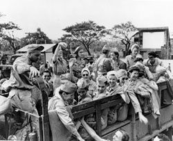 Manila during February 8-12, 1945. U.S. Army Nurses from Bataan and Corregidor, freed after three years imprisonment in Santo Tomas Interment Compound, climb into trucks as they leave Manila, Luzon, P.I., on their way home to the U.S. The nurses are wearing new uniforms given to them to replace their worn out clothes. [12 February 1945]