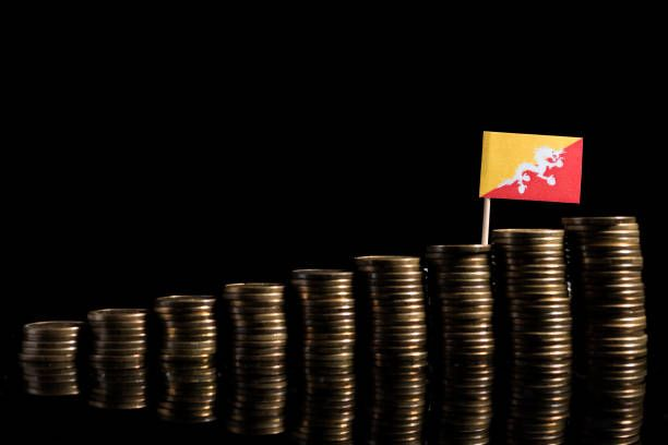 bhutan flag with lot of coins isolated on black background