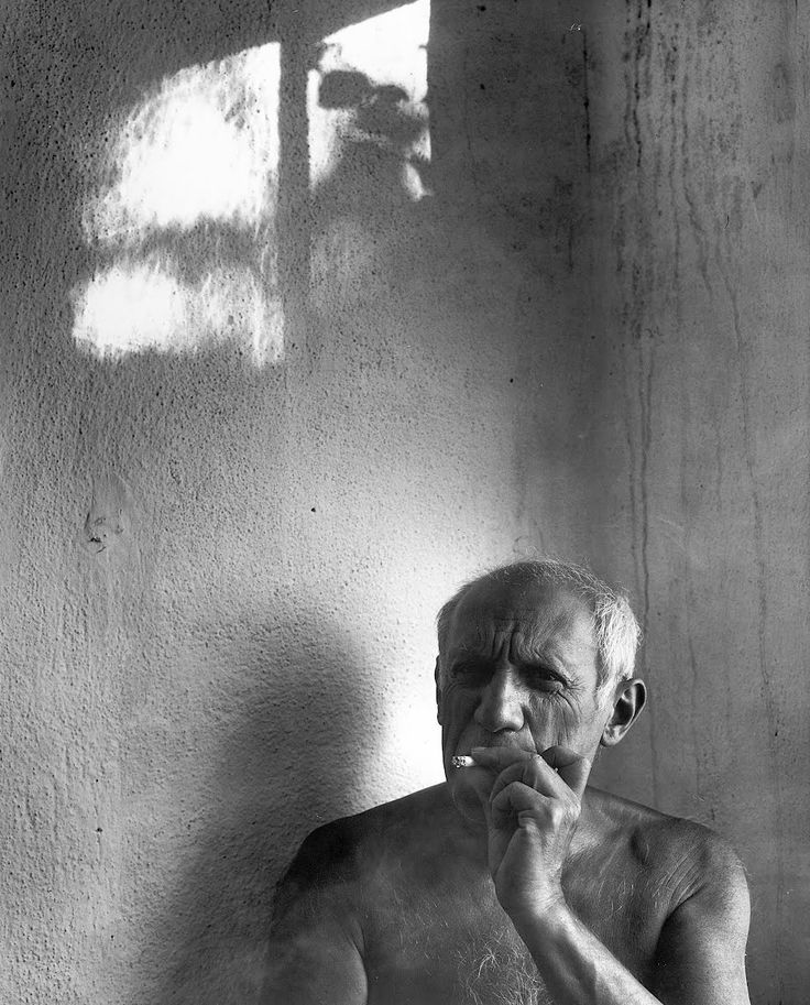 Artist Pablo Picasso, bare-chested & smoking cigarette.