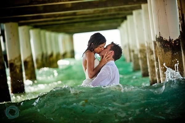 "This trash the dress photo gives ""under the boardwalk"" a whole new meaning. Grab your guy and head under a pier to steal a sweet kiss."