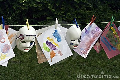 A line of childrens paintings and masks hanging on a line to dry