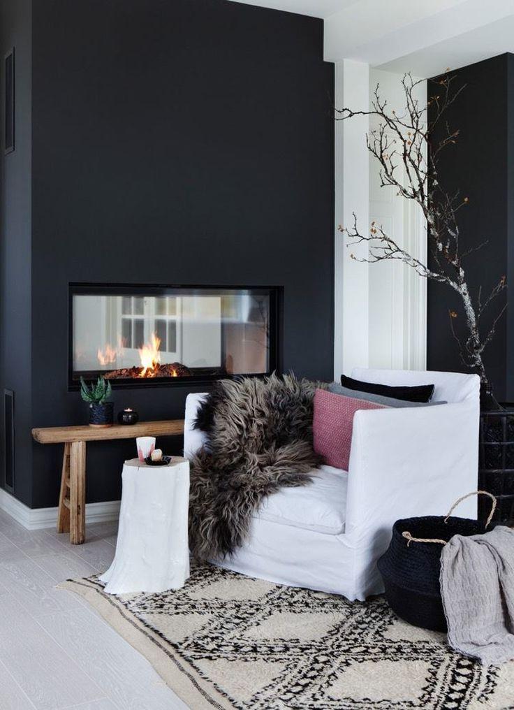 pan de mur en noir autour de la cheminée moderne,fauteuil blanc décoré de coussins et un plaid en fausse fourrure
