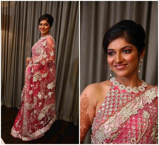 Elegant and sexy in a sweet pink saree with halter neck blouse at a wedding.