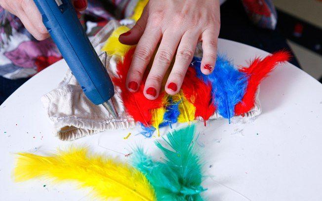 Com cola quente, aplique as penas coloridas ao longo do elástico. Foto: Tricia Vieira/Fotoarena