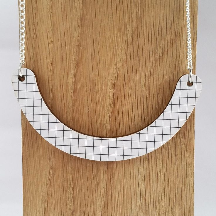 Simplicity is key in this minimal necklace.This versatile necklace is designed to be worn 2 ways. For days when you want to make more of the statement, the front of the necklace features a minimal grid print.For those more understated days, the reverse of the necklace is plain wood cut into clean, simple lines to create a necklace with understated elegance.The pendant has been treated with a varnish to protect the wood.The wooden pendant hangs from a silver plated cu...