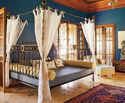 With the open iron bed and airy sheers, this room feels open and airy, even with the darker blue walls. Exposed wood surfaces are key in British Colonial design.