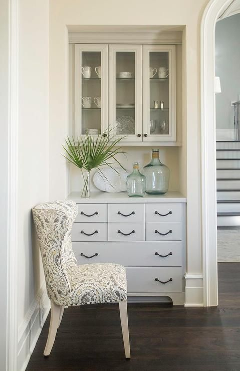 Chic dining room features a nook filled with a glass built in china cabinet over a gray built-in sideboard lined with recycled glass bottles.