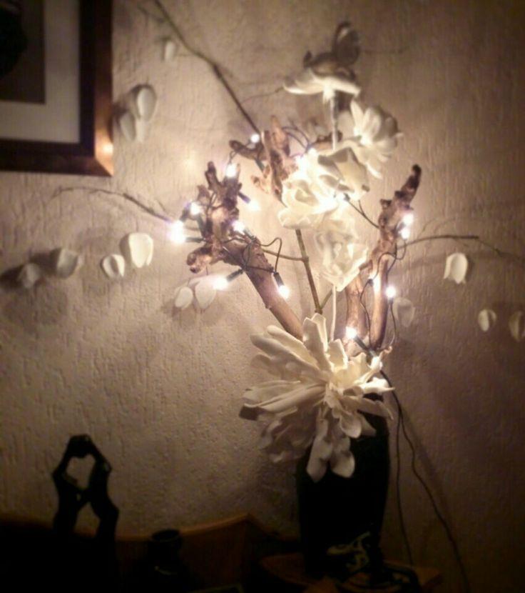 Sfeervol bloemstuk      Tak als basis, mooie witte foam bloemen en kerst verlichting