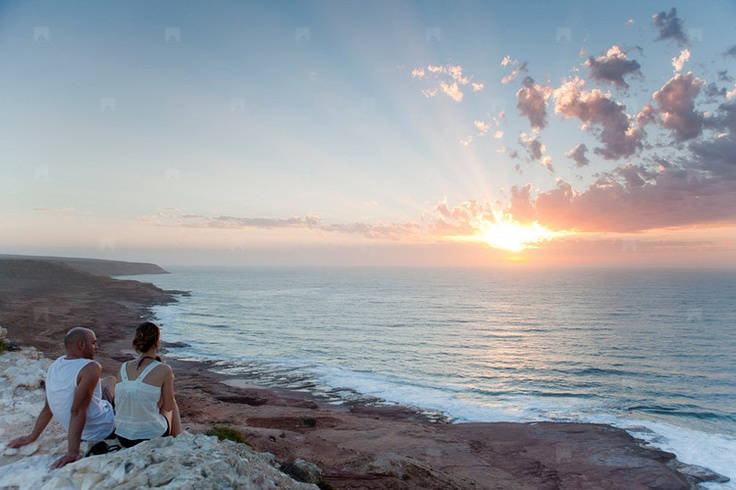 Couple sitting at Red Bluff, Kalbarri, Western Australia.