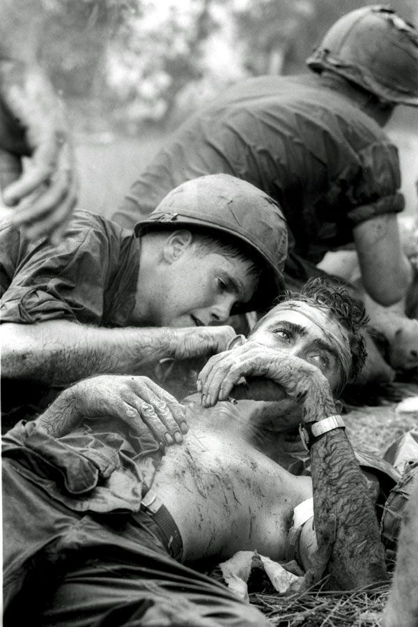 With sniper fire still passing overhead, medic James E. Callahan of Pittsfield, Mass., treats a U.S. infantryman who suffered a head wound when a Viet Cong bullet pierced his helmet during a three-hour battle in war zone D, about 50 miles northeast of Saigon, June 17, 1967. Thirty-one men of the 1st Infantry Division were reported killed in the guerrilla ambush, with more than 100 wounded. (Follow link for story)