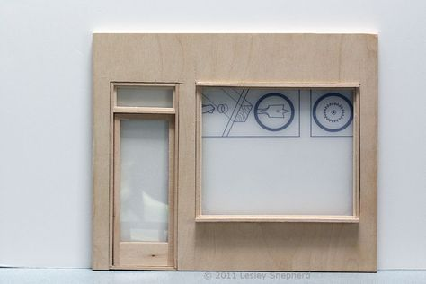 Large plain plastic window fitted to the front of a dolls house shop.