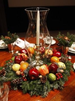 Holiday Decor with simple wreath decorated with fruit, pine cones, & holly berries.  Place a hurricane in the middle with taper candle inside.