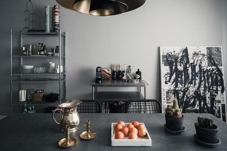 Интерьер и атмосфера комнаты формируют детали декора - подсвечники, сервировочный столик из нержавейки, картина с графити, сетчатый промышленный стеллаж.
