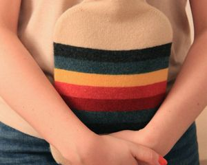 HOTTIE   DESIGN: OATMEAL BODY WITH BANDS OF CHARCOAL, MARINE, RED, PINK AND YELLOW   MATERIAL: MADE FROM 100% FINEST BRITISH SPUN LAMBSWOOL   FILLING: 'FASHY' BRITISH STANDARD 2L HOT WATER BOTTLE   KNITTED IN SCOTLAND