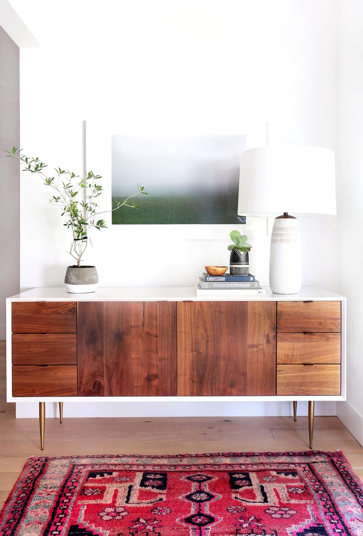 White walls, wood cabinet, white lamp, colorful wall art, plants, wood floors, and a red patterned rug