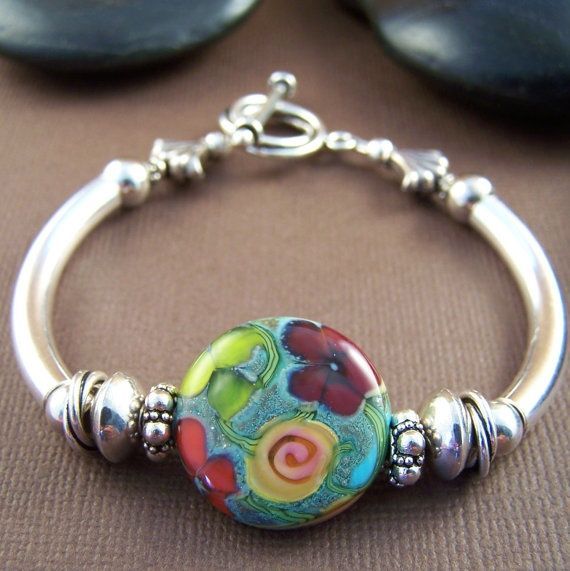 Artisan florals on glass with sterling curved tubes...one of a kind bracelet.