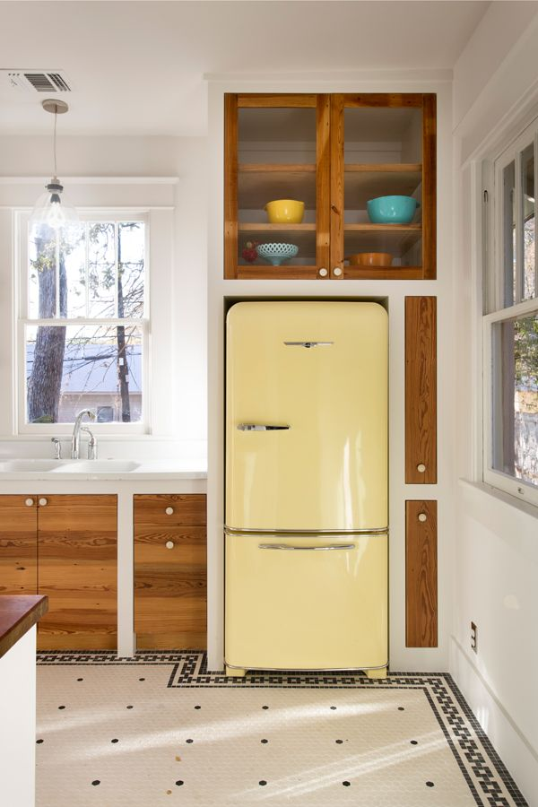A narrow pull-out pantry uses the space that allows room for the refrigerator door to open.
