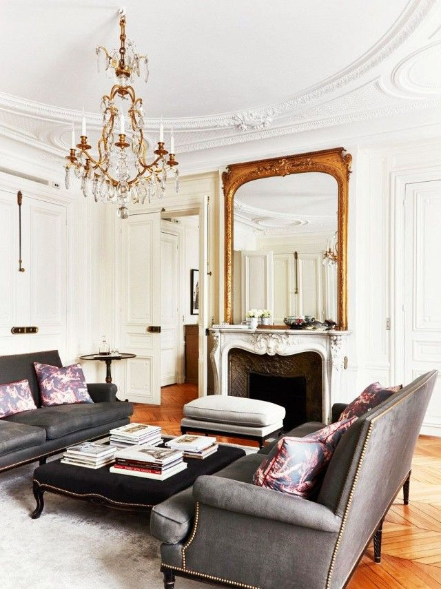 Elegant living space with classic architecture, a crystal chandelier, and  matching gray sofas