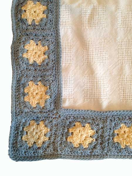 Organic cotton cot blanket in cream with a grey and yellow crochet border