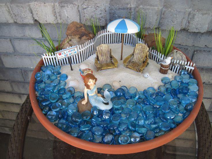 All it takes to make this beach themed fairy garden is a shallow plant container, blue pebbles from the Dollar Tree, and if you don't have any Florida sand, Dollar Tree carries sand as well.