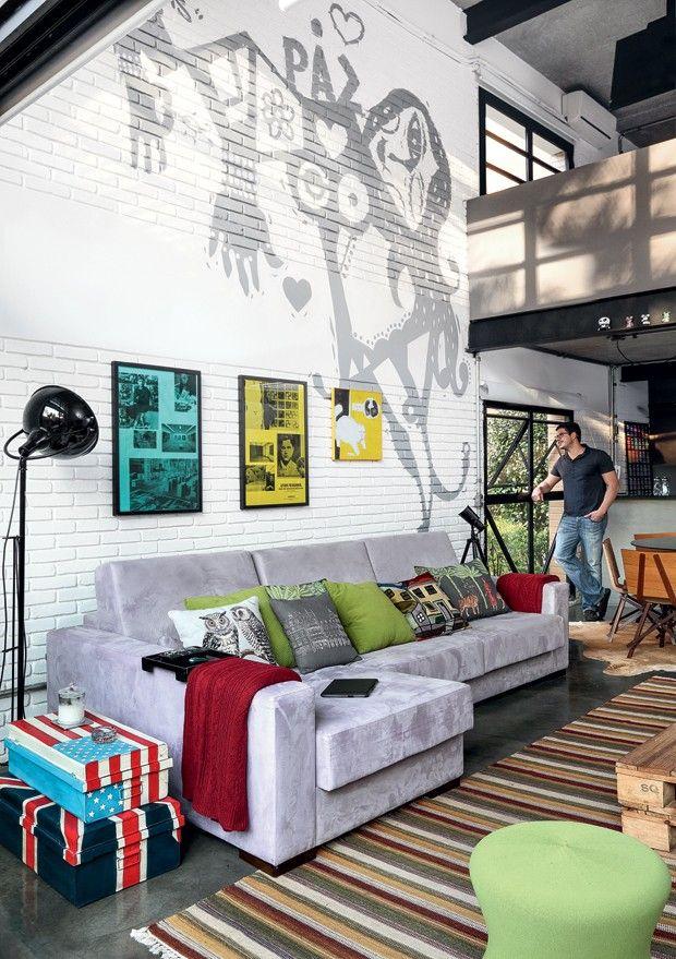 O morador Rodnei na janela. O grafite, de Bruno Dias, decora a parede atrás do sofá, da Gallery by Formato. Almofadas da Conceito Firma Casa. Da mesma loja são as malas e a luminária de piso. Manta Ralph Lauren e Tapete da Clatt (Foto: Evelyn Müller / Editora Globo)
