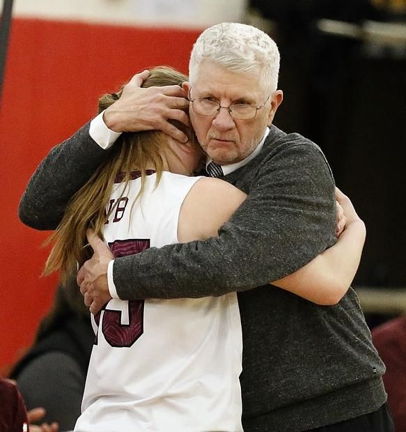 West Bridgewater High School girls' basketbal coach Steve Barrett gives Abby Bedard, player, a hug after the team lost in the Division 4 semifinal against Cathedral High School at Bridgewater-Raynham High School on Monday, March 7, 2016. — Dave DeMelia/The Enterprise