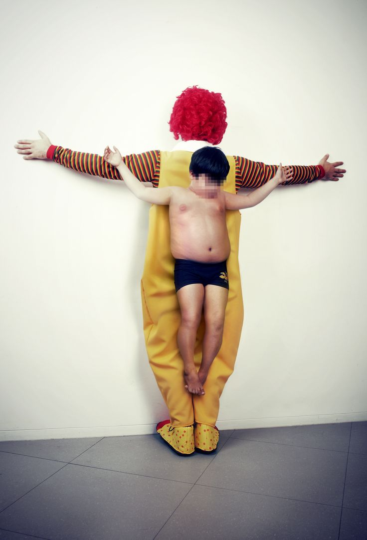 2013-09-10-mckdonalds.jpg Erik Ravelo Each work features both a child and an adult posed to demonstrate a contemporary evil, whether it be gun violence, molestation or the threat of nuclear war. Each work features a child being crucified on the back of an adult, each scene attempting to tell a different story about the loss of innocence. The human sculptures are then photographed with the child's face blurred, resulting in images as visually jarring as they are conceptually saddening.