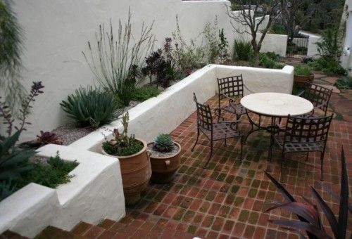 White stucco with brick or terracotta floors are the classic choice for a Spanish courtyard garden. This planter wall creates a cozy nook for dining and the perfect backdrop for sculptural, drought-tolerant plantings. A brick-toned flagstone path leads you out the gate.