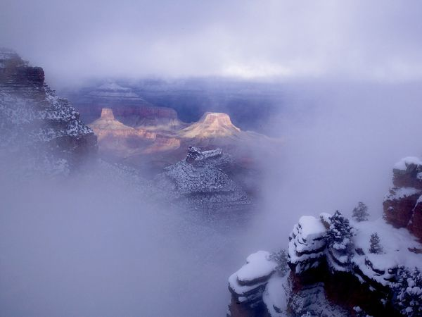 Grand Canyon National Park, Arizona  Photograph by Michael Nichols, National Geographic    Bad weather makes great pictures. The best bad weather is a stormy day, when the sun is battling the clouds and often breaks through to ignite one part of the scene. In this winter shot of the Grand Canyon by Michael Nichols, it is the single touch of sunlight that makes the photograph work. —Annie Griffiths