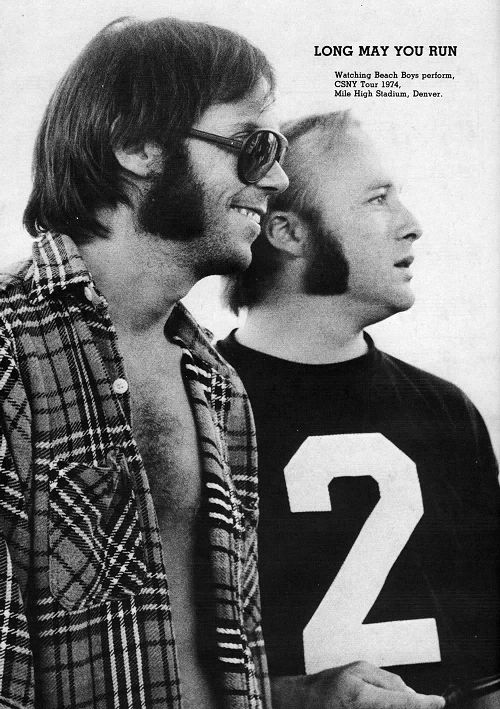 """memesouslapluie: """"  Neil Young and Stephen Stills watching the Beach Boys perform at Mile High Stadium, Denver, 1974 """""""