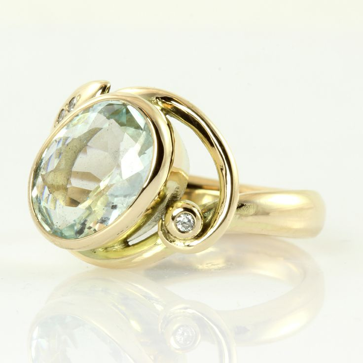 Gold ring with pastel aquamarine and leaf. A big and beautiful light blue aquamarine takes the center stage of this opulent gold ring, flanked by glittering diamonds on a shiny leaf.