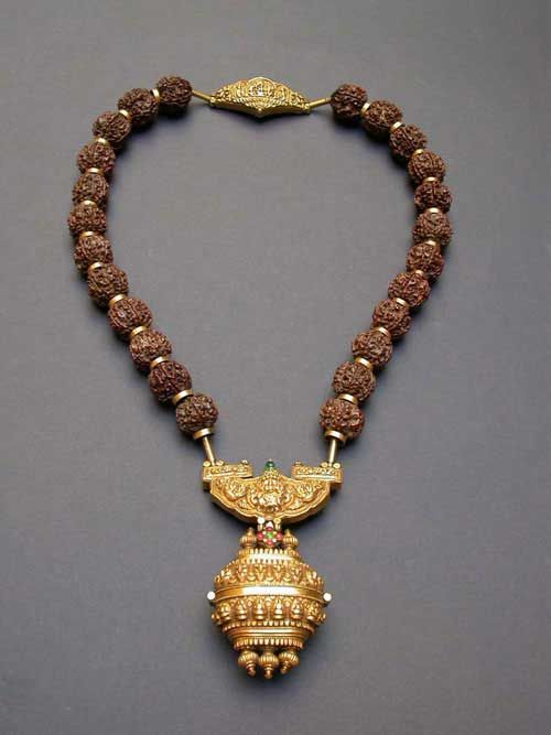 Tamil Nadu, India | Gowrishankaram from the 19th century |  Rudraksha beads with a gold repousse pendant and 22kt gold beads | Worn by Shaivite priest only on a special cerimony.   The central unit depicts Shiva and Parvati on the bull Nandi, the box is a container for a movable lingam or sacred ashes.