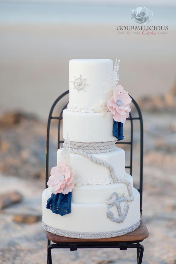Nautical themed cake with pale pink flowers and navy handkerchiefs with fondant rope, anchor, and wheel
