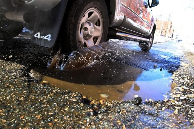 A vehicle tries to avoid a 4-foot-wide pothole on Snow Street in Providence on Wednesday. Providence residents are encouraged to report potholes to the mayor's Office of Neighborhood Services.    The Providence Journal/Bob Thayer