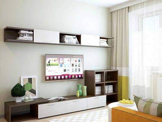 В гостиной, которая является и спальней, стены разные – две однотонные белые, а третья  – белая с черными латинскими буквами. На полу – ламинат + ковер. Из мебели здесь яркий оранжевый диван-кровать, стенка, платяной 4-дверый шкаф для хранения одежды, рабочий стол и стул.