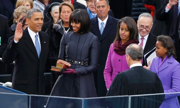 Supreme Court Chief Justice John Roberts administers the oath of office to President Barack Obama as first lady Michelle Obama holds the bible and daughters Malia and Sasha look on.