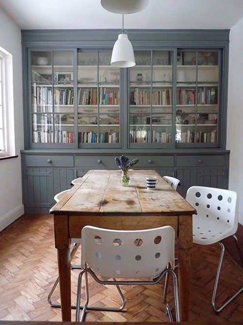 gray antique cabinet, pine farmhouse table, simple modern chairs and light fixture