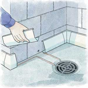 Interior gutter systems catch basement water and channel it to floor drains or a sump pump. Epoxy seals the channel to the floor; the same glue can create curbs to route the flow to a drain.