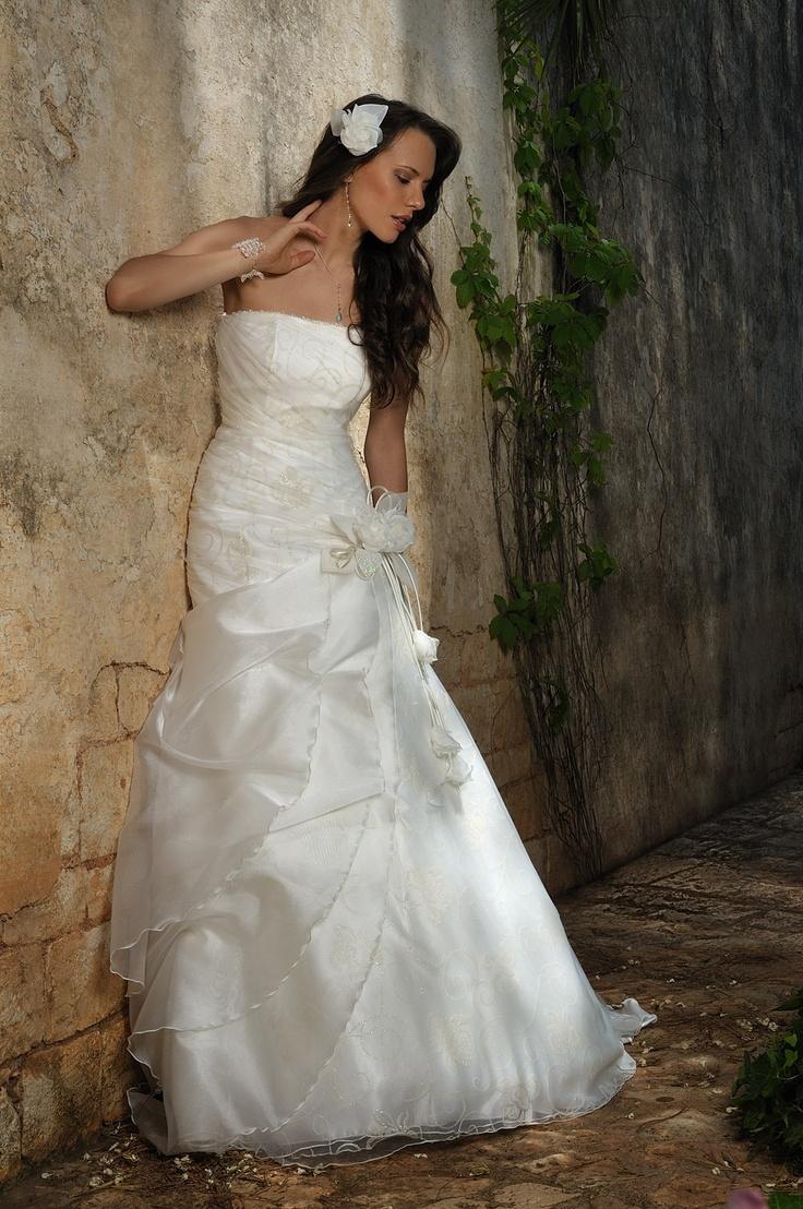 abito di linea vintage con gioco di organza e tulle drappeggiato su sfondo di rose glitterate.
