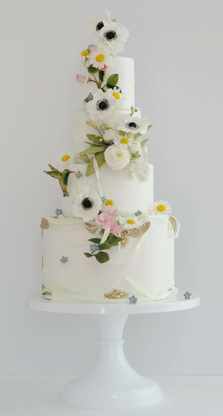 White tiered cake with spring flowers, sugar white poppies, and a hummingbird | by Maggie Austin Cake