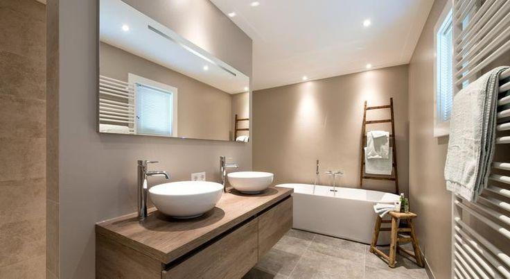 (@ Middelkoop Culemborg / Badkamers) Deze ruime badkamer is helemaal af. Een mooi meubel met kommen, en vrijstaand bad in de zelfde stijl en warme kleuren.   Ook hier is alleen het nodige betegeld, dat geldt dus voor de douche die te vinden is achter het badkamermeubel.    https://www.middelkoopculemborg.nl/badkamers/klantervaringen-badkamers/familie-brink/