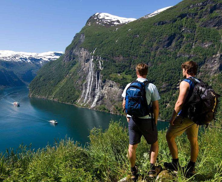 Zwei Männer stehen am Berg des Geirangerfjords Panoramablick auf den Fjord und die Berge, zwei Schiffe auf dem Wasser, digitaler Reiseführer Skandinavien Rundreise PaulCamper