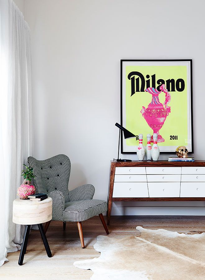 Pink and yellow 'Milano' vintage poster in black frame, black AJ reading lamp, wood and white mid-century modern sideboard/buffet, black and white herringbone fabric upholstered tufted armchair with wooden legs, pale wood and black side table, timber floorboards