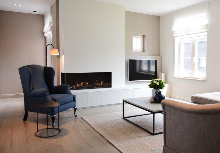 Durf strak modern te combineren met een landelijke stijl. Deze prachtige blauwe fauteuil is een tijdloze eyecatcher in dit interieur en past perfect bij de rechte lijnen van de open haard en salontafel.