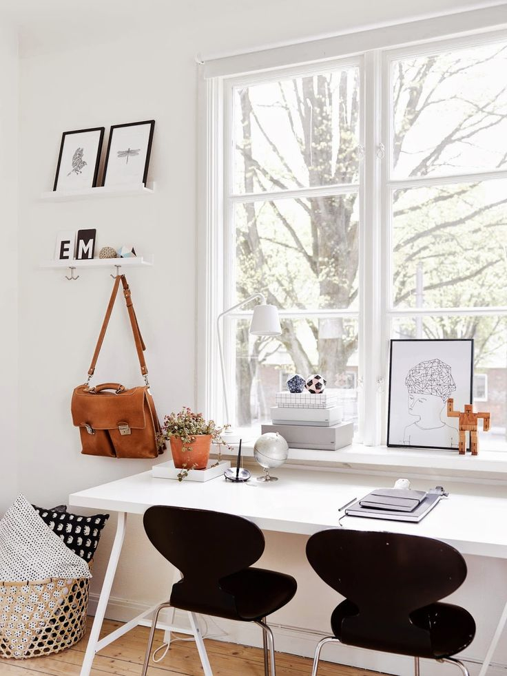 Tidy and organized white desk in front of a big window. Light colors and symmetric arrangements help to enjoy your home office.