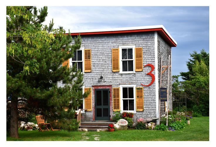 Galerie d'art située à Kamouraska, l'un des plus beaux villages du Québec, dans une coquette dépendance d'autrefois. Mise en valeur de l'architecture d'une maison d'été datant de 1930, un carré de 20 pi x 20 pi, sur deux étages. Couverture de bardeau naturel et d'époque. Volets jaunes ocres et accents décoratifs rouges.