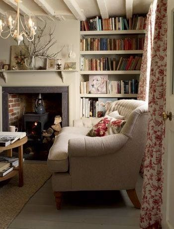 Beams rainbow bookshelves library wood burner fireplace exposed bricks armchair