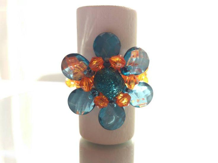 Anillo diseño flor de pétalos, tejido en naranjo y azul.